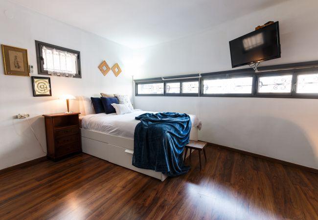 Великолепная спальня с большой комфортабельной кроватью и телевизором в квартире на ул. Бен Иегуда